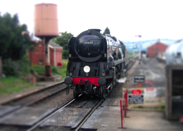 Black steam train approaching a foot crossing.