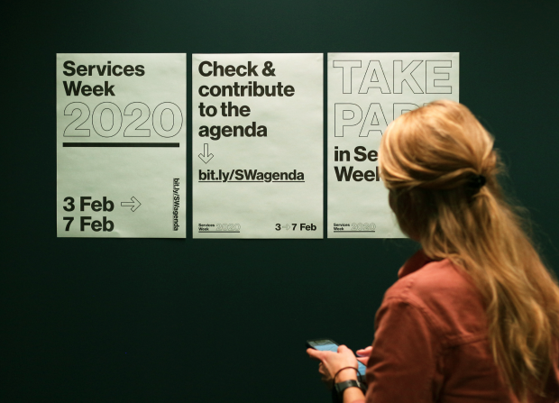 A woman holding a phone while looking at posters for Services Week 2020. She looks at one poster saying 'Check & contribute to the agenda', which includes an internet address to the open agenda: bit.ly/SWagenda