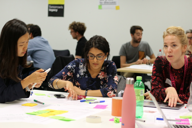Various people participating in service design training. Three young women in the front are collaborating on a task, using colourful sticky notes