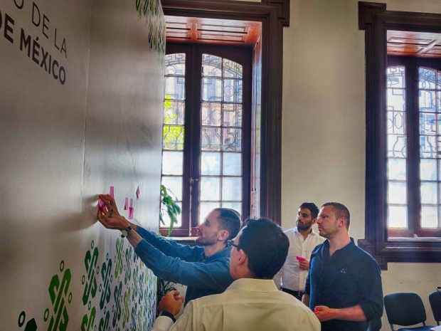 People are putting post-it notes on a wall
