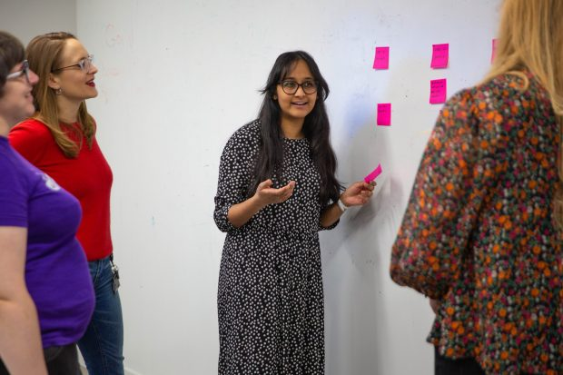 Four women at a workshop with sticky notes.
