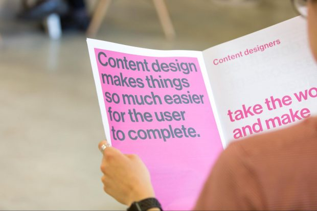 "A person is holding a printed booklet. The left page reads ""Content design makes things so much easier for the user to complete."" The right page reads incomplete text."