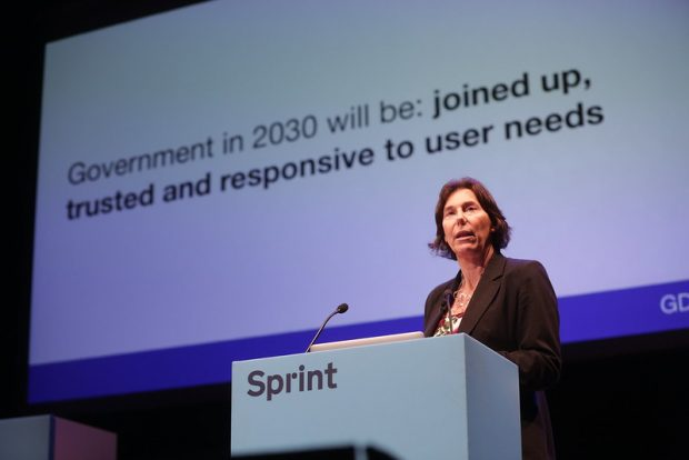 "Alison Pritchard stands at a Sprint-branded lectern, and on the screen behind her is the text ""Government in 2030 will be: joined up, trusted and responsive to user needs""."