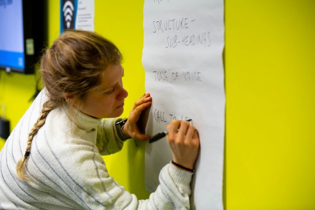 "A women is writing on a piece of paper fixed on a wall. She has written the following bullet points: ""Structure - subheadings"", ""Tone of voice"", and she is beginning to write ""Call to action""."