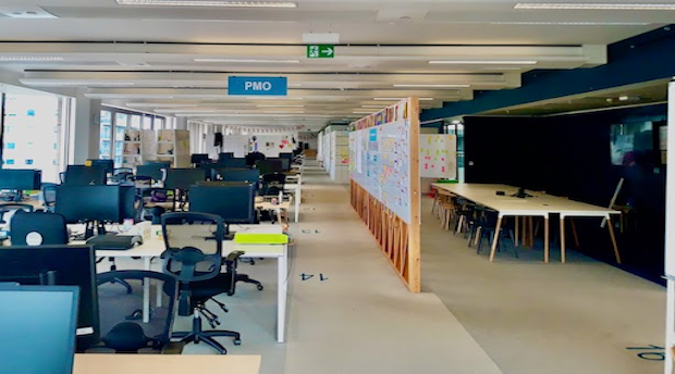 Empty work spaces at the GDS offices showing rows of desks and whiteboards with post-it notes.