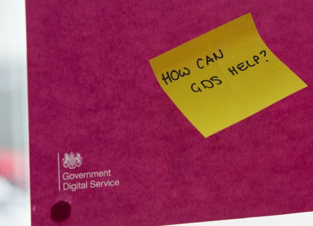 "A sticky note reading ""How can GDS help?"" stuck on a poster with the Government Digital Service (GDS) logo."