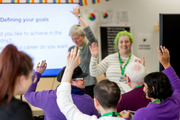 """Two members of staff are presenting to colleagues on """"Defining your goals"""", with many members of staff raising their hands."""